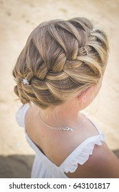 French braid hair plait of blonde little girl in white dress with beach sand in background top view