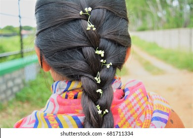 French braid hairstyle decorated with white flowers on black/brunette Indian hair