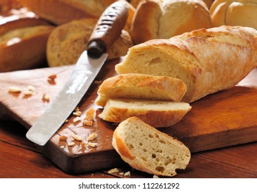 French bread baguette cut on vintage wooden bread board with knife. Selective focus with background of assorted bread rolls.
