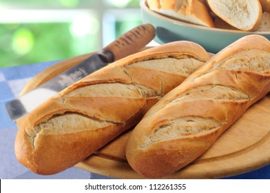French bread baguettes on bread board and bread-knife
