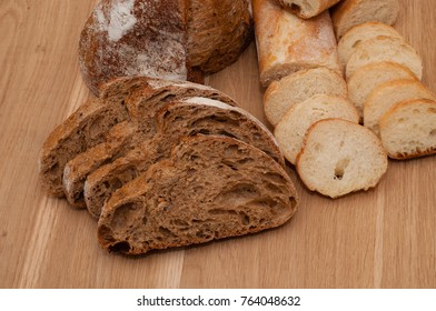 French bread, loaf and ciabatta sliced on wooden board with space for text