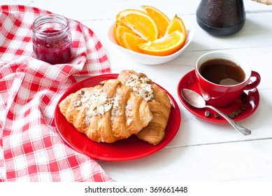 French breakfast - coffee, croissants, fruits  and jam on white wooden table.