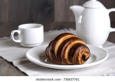 French breakfast with croissant and coffee, white porcelain coffee pot and coffee cup on gray wooden with background
