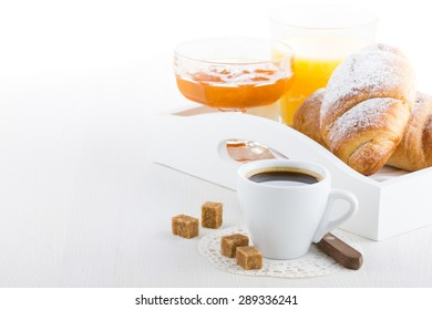 French breakfast with croissants, apricot jam, coffee and orange juice served on white wooden table