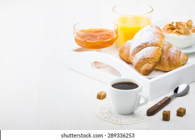 French breakfast with croissants, apricot jam, coffee, orange juice and natural yogurt with cornflakes served on white wooden table