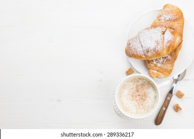 French breakfast with croissants and coffee served on white wooden table
