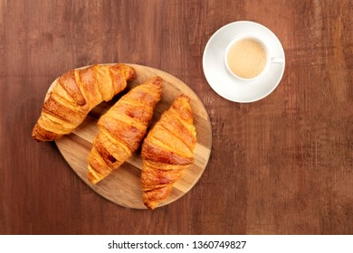 A French breakfast with croissants and coffee, shot from the top on a dark rustic wooden background with a place for text