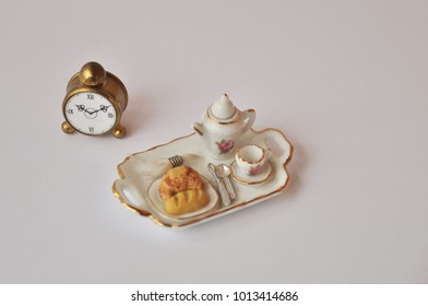French breakfast in miniature. A teapot with a cup, on a plate of kroasan and a slice of bread. miniature cookware