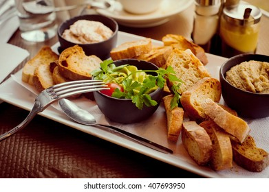 French breakfast for two in a Parisian street cafe - baguette, guacamole and salmon rillettes