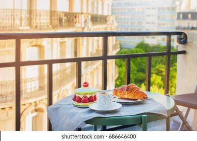 French breakfast with a view. Cup of coffee espresso, croissant and big macaron with raspberries.
