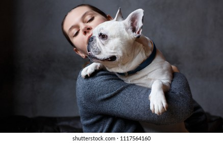 French bulldog on the hands of his master. It is felt that the girl loves her pet and hugs him tightly. The dog is used to such a nuisance and sits quietly in the arms of a girl.