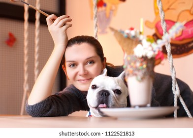 French Bulldog on his birthday with his own master. In the room there are many decorations, on the table there is ice cream with candies, a holiday and a good mood are felt.