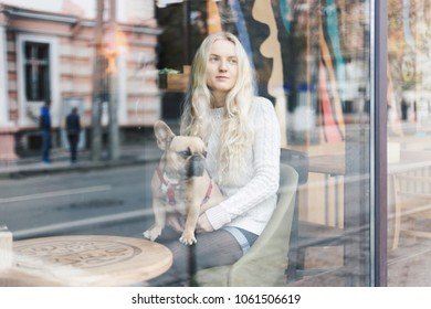 French bulldog relaxing in a cafe on blonde stylish woman's lap. View through the window