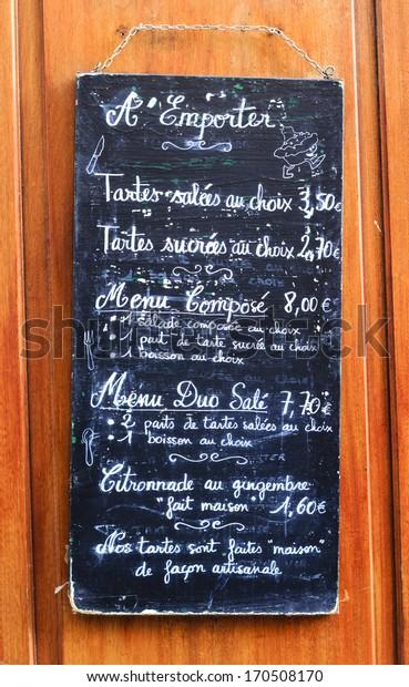 French cafe menu board handwritten in chalk on blackboard hanging on the wall at the sidewalk in Paris, France
