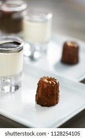 French cake canele on a plate and vanilla cream on a glass
