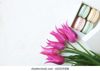 French candy macarons in present box with purple tulips on white textured backgrouud. Flat lay. Copy space.