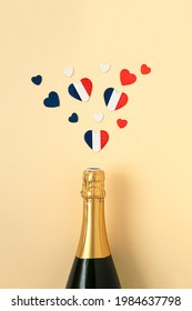 French champagne bottle and hearts in the colors of the French flag, top view, Bastille Day and French National Day concept