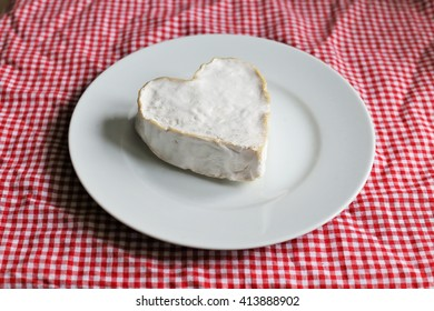 A French cheese in a shape of a heart on a plate with a picnic tablecloth
