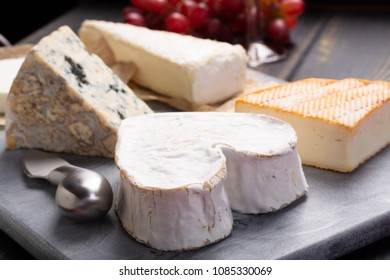 French cheeses plate in assortment,  Neufchatel heart shaped aged white cow cheese from Normandy
