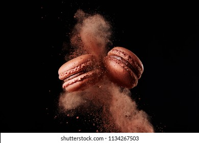 French chocolate macaron with cocoa powder against black background