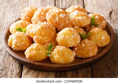 French Chouquettes with pearl sugar cooked according to a traditional recipe closeup on a plate on the table. horizontal