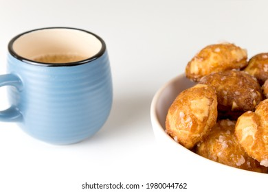 french chouquettes puffs with perles of sugar on plate with blue cup of coffee. Choux pastry Classic French bakeries.