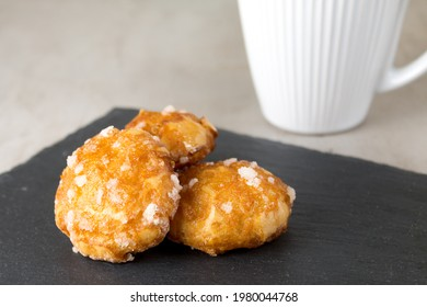 french chouquettes puffs with perles of sugar on black slate board with white cup of coffee. Classic French bakeries