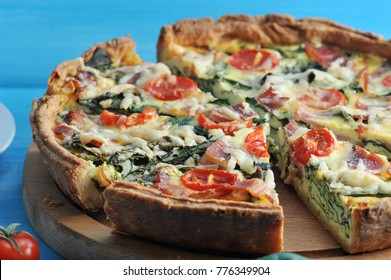 French classic pie quiche with spinach, bacon, cherry tomatoes and cheese. The pie on the wooden board is cut into portions. Blue background. Close-up. Macro photography.