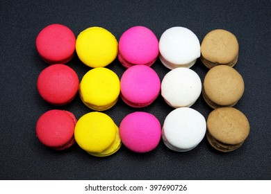 French colorful macarons on black background.