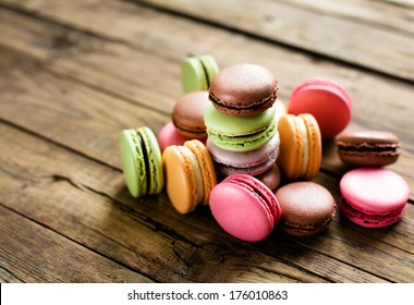 A lot of french colorful macarons on a woody floor