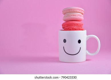 French colourful macarons with happy cup on pink pastel background. Romantic concept with copy space for design works. Sweet dessert for tea time or coffee break.Concept about love and relationship