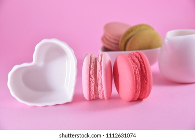 French colourful macarons on pink pastel background with love cup.Romantic concept with copy space for design work.Sweet dessert for tea time or coffee break. Idea for wallpaper or creative card