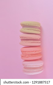 French colourful macarons on pink pastel background.Love and romantic concept with copy space for design work.Sweet dessert in soft style for creative card and wallpaper.Colourful background.