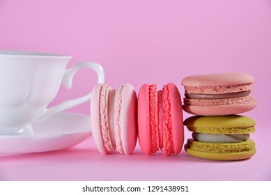 French colourful macarons in white ceramic cup on pink pastel background. Concept about love destination and relationship. Valentines's Day idea for card and wallpaper. Copy space for text