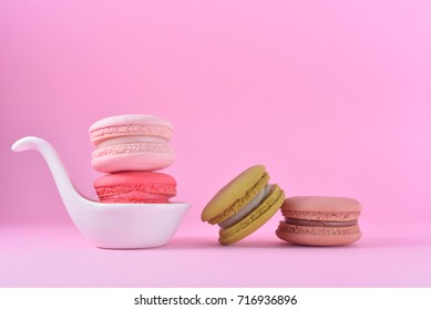 French colourful macarons in white ceramic cup on pink pastel background. Romantic concept with copy space for design works. Sweet dessert for tea time or coffee break time. Idea for wallpaper or card