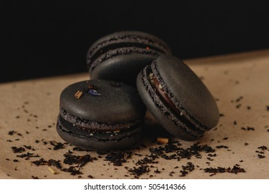 french cookies black macaroons on a black background