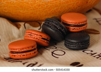 french cookies black and orange macaroons on a  background home interior