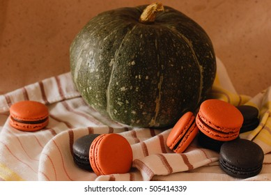 french cookies black and orange macaroons on a  background home interior with pumpkin