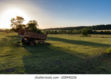 French countryside - Lorraine. Cow pasture with old trailer at sunset.