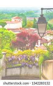 """French countryside. Picturesque view of Aubeterre sur Dronne (France), listed as """"One of the most beautiful villages in France"""" since 1993. Selective focus on the old lantern. Toned photo. Haze effect"""