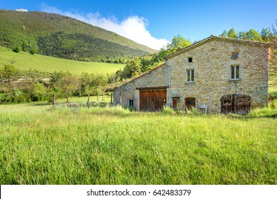 French countryside. Typical old farm with mountains in the background in Vercors, France.