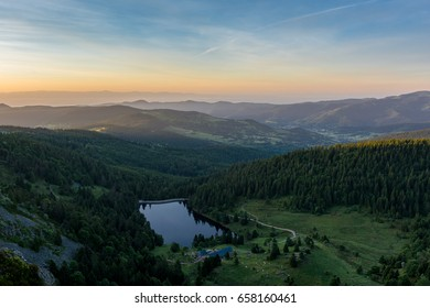 French countryside - Vosges. Sunrise in the Vosges with a view of the Rhine valley, a lake, the Black Forest (Germany) and the Alps in the background.