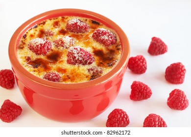 French creme brulee dessert with raspberries covered with caramelized sugar in red terracotta ramekin on white background