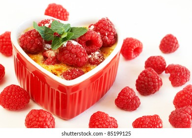 French creme brulee dessert with raspberries and mint covered with caramelized sugar in red heart shaped ramekin on white background