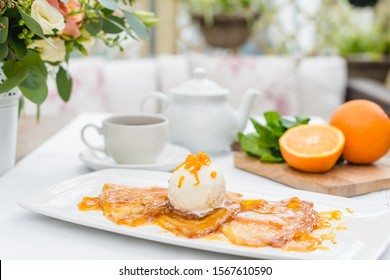 French crepe suzette pancakes with ice cream and orange sauce on a white plate