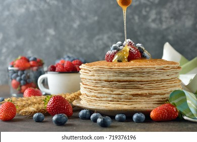 French crepes with berries and honey on a gray background