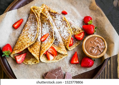 French crepes with chocolate spread and strawberries, tasty sweet dessert filled with chocolate cream and fresh strawberries fruits