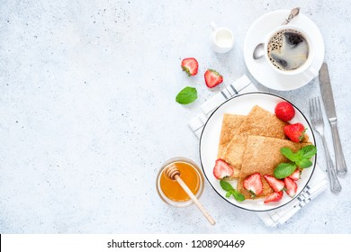 French Crepes or Russian Blini with fresh strawberries, honey, coffee on concrete background. Healthy Tasty Breakfast. Table top view, copy space