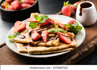 French crepes with strawberries and chocolate sauce on a plate served on wooden cutting board. Closeup view. Tasty sweet breakfast, lunch or dessert