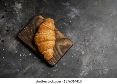 French croissant. Freshly baked croissants with jam on dark stone background. Tasty croissants with copy space